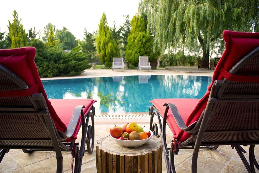 zwei Sonnenliegen am Pool, in der Mitte eine Obstschale