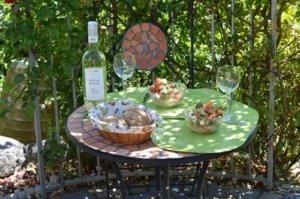 Sitzecke im Gründen mit zwei Gläsern Wein und ein wenig Gedeck